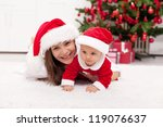 Our first christmas together - happy mother and baby girl in santa hats - stock photo