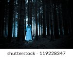 Horror Scene. Lady in white dress in a deep dark forest - stock photo