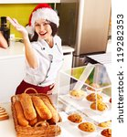 Female chef in Santa hat baking baguette bread. - stock photo