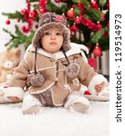 Christmas baby girl in front of te tree - stock photo