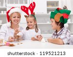 Happy family with seasonal hats making gingerbread christmas tree - stock photo
