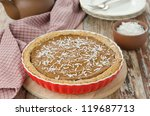 Pie with pumpkin and chocolate in ceramic form on a wooden table - stock photo
