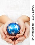Adult and child hands holding christmas bauble - holidays in  the family concept - stock photo