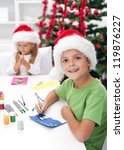 Kids making christmas and seasonal greeting cards in front of the decorated tree - stock photo