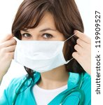 Portrait of a woman in doctor uniform wearing surgical mask - stock photo