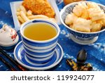 cup of green tea and japanese rice crackers assortment on the table - stock photo