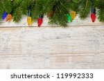 Multicolored Christmas lights on spruce branch with wooden background - stock photo