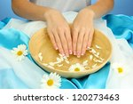woman hands with wooden bowl of water with flowers, on blue background - stock photo