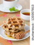 stack of waffles with maple syrup for breakfast, mint tea in the background - stock photo