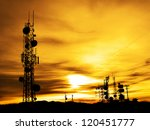 Several radio towers with sunset sky in background - stock photo
