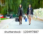 happy women walking the city street with shopping bags - stock photo