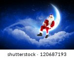 Photo of Santa Claus sitting on shiny moon above winter forest - stock photo