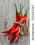 Bunch of fresh hot chili on an old wooden board. - stock photo