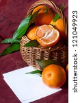 Sweet ripe tangerines in a wicker basket and note. - stock photo