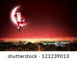 Santa Claus on the moon above a city at night - stock photo