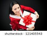 Portrait of a pretty brunette woman with Christmas present on dark background, view from above - stock photo