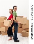 Couple moving in to a new home - carrying cardboard boxes - stock photo