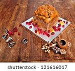 Christmas cake with red berries and metal tips and xmas decorations - stock photo
