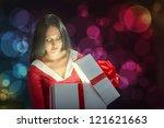 Pretty brunette woman opening the magic Christmas present box - stock photo