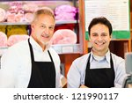 Butchers in a supermarket at work - stock photo