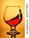 Glass of splash cognac on yellow background - stock photo
