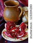 Ripe sweet pomegranate on a rustic plate. - stock photo