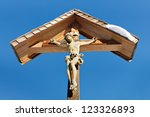 Wooden wayside cross with a clear blue sky background. - stock photo