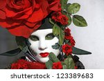 VENICE - 14 FEBRUARY: An unidentified woman with a white mask dressed like a red rose perform at the most famous European Carnival on February 14, 2010 in Venice. - stock photo