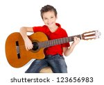 Pretty happy  boy is playing on acoustic guitar - isolated on white background - stock photo