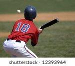 Baseball player wearing uniform bunting a baseball while at bat - stock photo