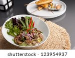 Asian style Thai salad with steak and chicken satay barbecued chicken on skewers appetizers in the background. - stock photo