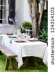 Simple rustic country style table setting for a party gathering in a casual outdoor garden setting - stock photo