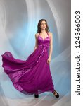 Beautiful young woman in plum violet evening dress, on grey background - stock photo