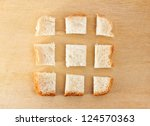 slice of bread chopped in pieces on wooden table - stock photo