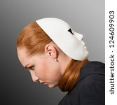 Two faces. Red head woman with white mask worn on the back of her head - stock photo