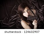Portrait of pretty young woman nibbling the bar of chocolate, view from above, brown background - stock photo
