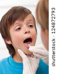 Boy showing her throat to health professional sticking his tongue out - stock photo