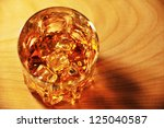 Glass of whiskey with ice on a wooden table top view - stock photo
