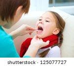Doctor is examining a little girl, indoor shoot - stock photo
