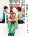 Sad little girl sitting excluded by the other kids - stock photo