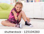 Little girl learning how to tie her shoes, being proud of herself - stock photo