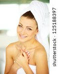 Sweet young woman wrapped in towel with hands on her body - stock photo