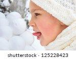 Girl licking snowballs - stock photo