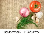 Photo of tomato onion and garlic vegetables on sacking background texture - stock photo