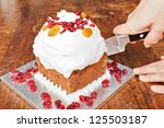 Cutting christmas cake in two slices with a metal knife - stock photo