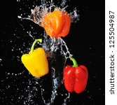 Three peppers water splash on black - stock photo