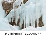 Icicles at a frozen waterfall in the Alps, South Tyrol, Italy. - stock photo