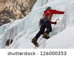 PRAGS, ITALY - JANUARY 27: An ice climber works his way up a frozen waterfall on January 27, 2012, near Prags, Italy. The area is one of the premiere destinations for ice climbing in Europe. - stock photo