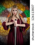 Portrait of posing woman in medieval dress with the sword - stock photo