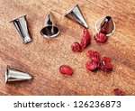 Pastry bag metal tips and red candieds on a wooden table - stock photo